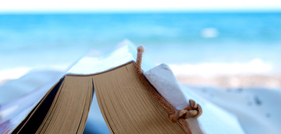 Best gay books featured image, an open book on a sunny beach