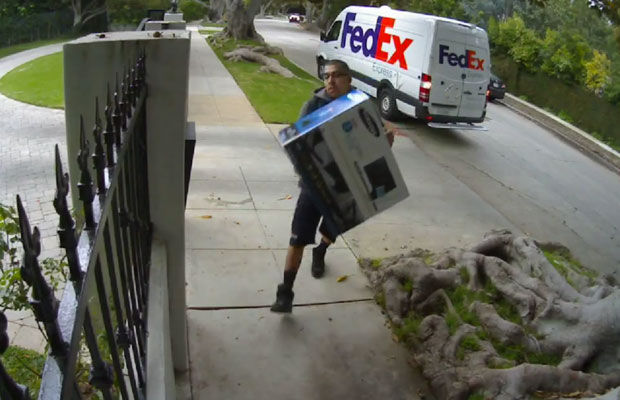 Fed Ex guy throwing computer screen over gate