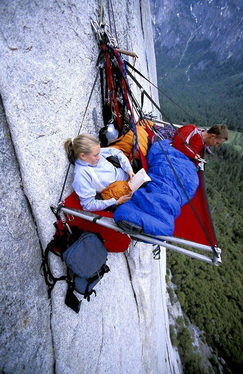Two rock climbers suspended on a mid air portaledge